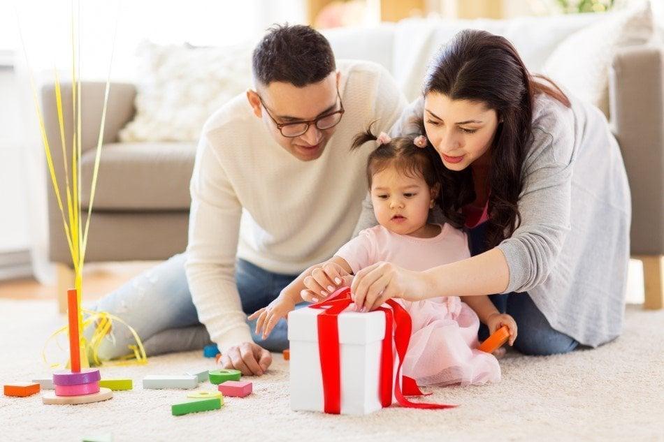 Baby der er ved at pakke sin fødselsdagsgave op - med hjælp fra sine forældre