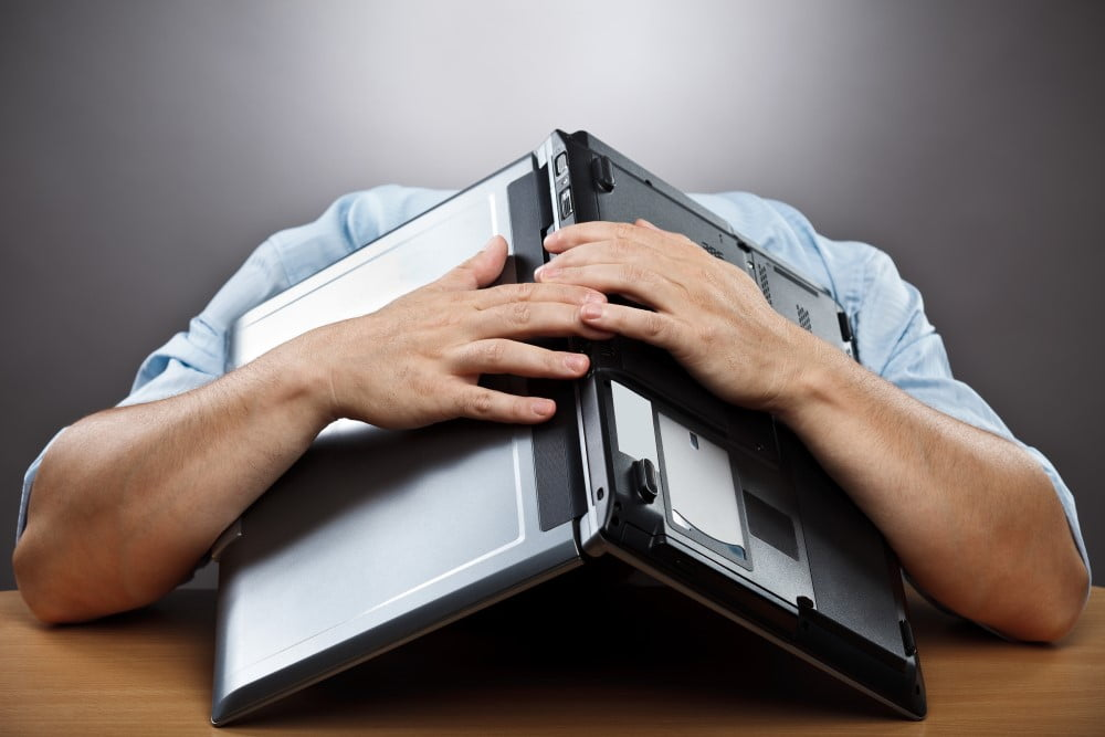 Mand gemmer sig bag computer